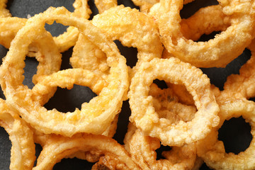 Homemade crunchy fried onion rings on table, top view