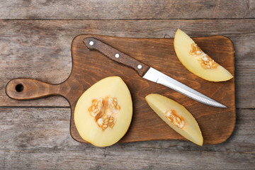 Flat lay composition with sliced ripe melon on wooden background
