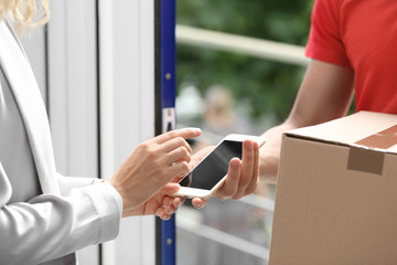 Woman using smartphone app to confirm receipt of parcel from courier near door