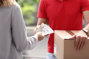 Woman paying courier for delivered parcel on doorstep
