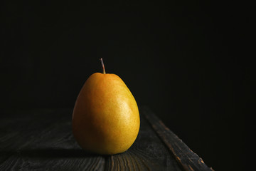 Ripe pear on wooden table against dark background. Space for text