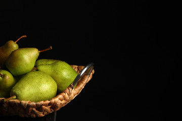 Tray with ripe pears on table against dark background. Space for text