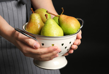 Woman holding colander with ripe pears on black background, closeup