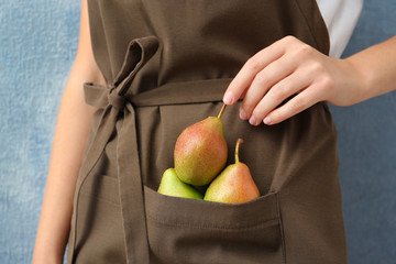 Woman in apron with ripe pears on color background, closeup