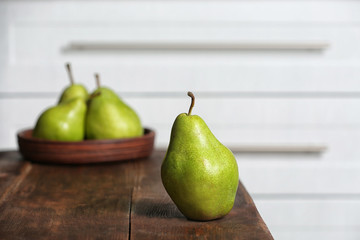 Ripe pear on wooden table against blurred background