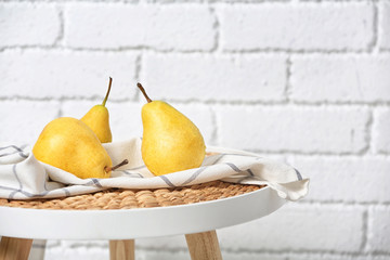 Ripe pears on table near brick wall. Space for text