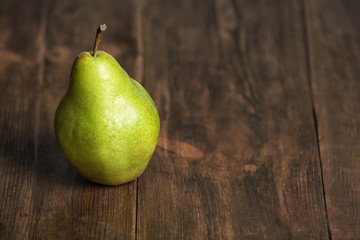 Ripe pear on wooden background. Space for text