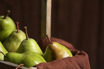 Tasty ripe green pears in basket, closeup