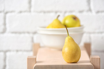 Ripe pear on wooden shelf against blurred background. Space for text
