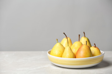 Plate with pears on table against grey background. Space for text