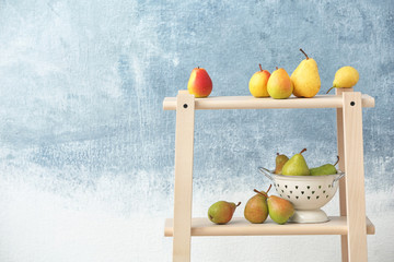 Shelving unit with ripe pears on color background. Space for text