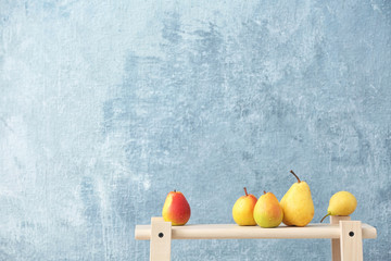 Ripe pears on wooden table against color background. Space for text