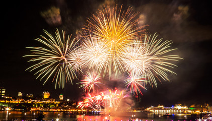 White, green, and yellow fireworks in front of Quebec City during a summer festival.