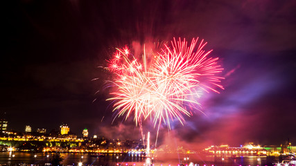 Bright red and pink fireworks during a summer festival in Quebec City, Canada.