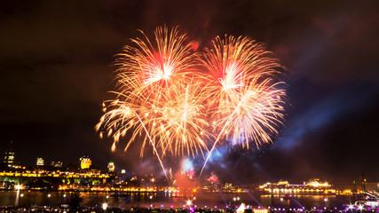 Orange and golden fireworks in front of Quebec City during a summer festival.