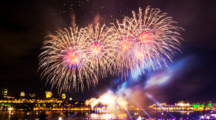 Red, blue, and gold fireworks in front of Quebec City during a summer festival.