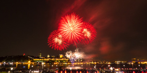 Red fireworks in front of Quebec City during a summer festival.