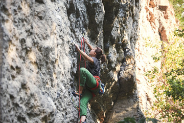young woman rock climber climbing on the cliff