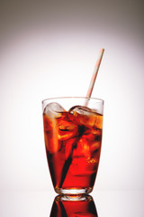Cola in glass with ice on grey background