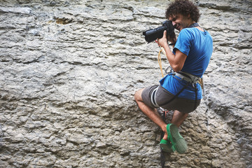 the photographer hangs on a rope on the cliff and shoots rock climbers
