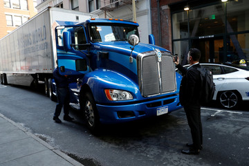 A man photographs a Toyota Project Portal hydrogen fuel cell electric semi-truck during an event in San Francisco, California