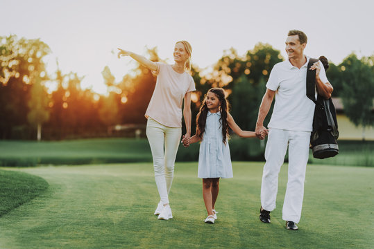 Happy Young Family Relax on Golf Field in Summer.