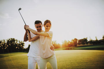 Young Happy Couple Playing Golf on Field in Summer