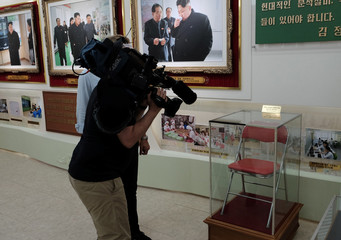 A television news cameraman films a chair once used by North Korean leader Kim Jong Un and now preserved at an exhibition at a cosmetics factory in Pyongyang