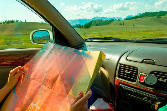 The girl rides in the car in the passenger seat and looks at the paper map looking for the desired route and indicates the road while traveling through the mountains of the Altai