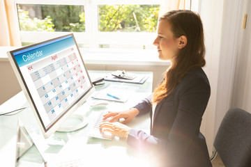 Fototapete - Businesswoman Looking At Calendar On Computer