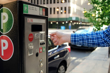 man is paying his parking using credit card at  parking pay station terminal