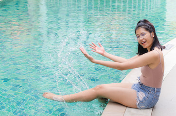 thai girl sitting at poolside