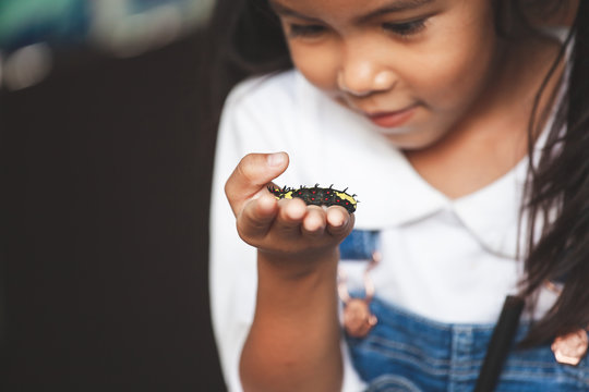 Cute asian child girl holding and playing with black caterpillar with curious and fun. Black caterpillar crawling on her hand.