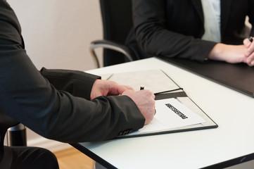Ein Mann unterschreibt einen Arbeitsvertrag