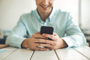 Digital device. Close up of a modern smartphone being held by a joyful young man