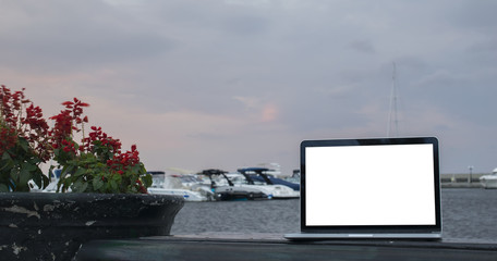 computer laptop with blank white screen on wooden table with yacht boats floating on the sea at background