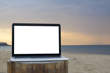 Laptop with blank screen on table of Blur summer white sand beach