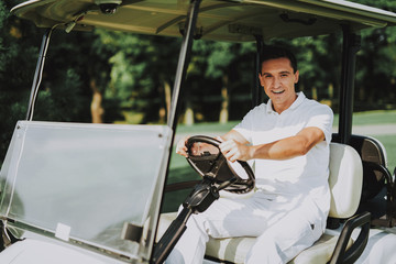 Young Man in White Shirt using Cart on Golf Field.