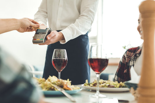 Payment with card. Nice professional waiter holding a money terminal while taking a payment