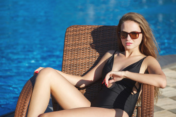 Young woman in a black swimsuit and glasses is bathing in a deck-chair near the pool with blue water in the resort hotel.