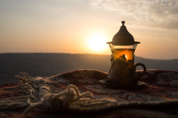 Arabian tea in glass on a eastern carpet. Eastern tea concept. Armudu traditional cup. Sunset background. Selective focus Wall mural