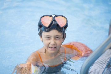 Little girl 6 years swimming in the outdoor pool