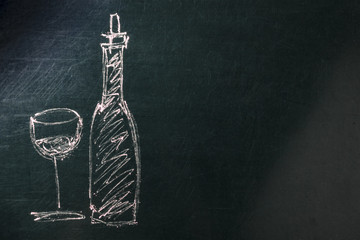 A photo of a simple drawing of a glass and a bottle of wine, made with chalk on a blackboard, with copy space