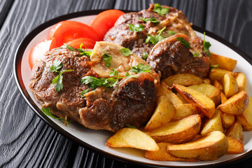 shank Ossobuko with a garnish of fried potato slices and fresh tomatoes close-up on a plate. horizontal