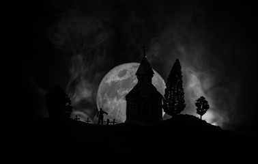 Scary view of zombies at cemetery dead tree, moon, church and spooky cloudy sky with fog, Horror Halloween concept.