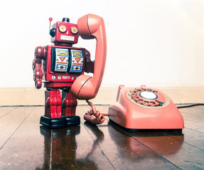 big red robot on the phone standing on a old w