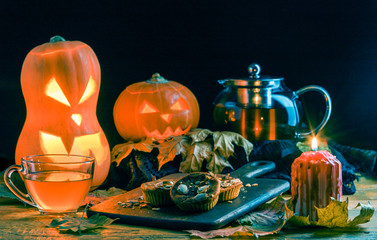 Photo of halloween pumpkins, cakes, cup of tea