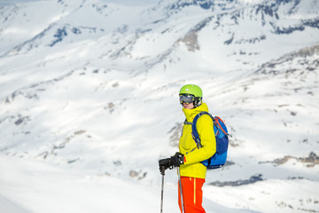 Photo of sportive man skiing against background of snowy mountains