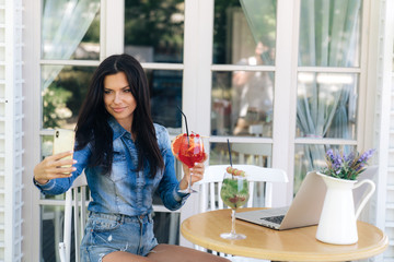 Attractive brunette with long hair, has a European appearance, stylishly dressed in jeans, makes selfie on a smartphone with a glass of grapefruit juice.