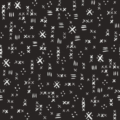 Hand drawn white tribal marks, cross stitches on dark background vector seamless pattern. Abstract geometric print
